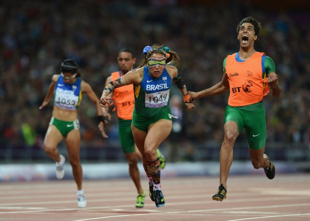 LONDON, ENGLAND - SEPTEMBER 05: Terezinha Guilhermina of Brazil and guide Guilherme Soares de Santana cross the line to win gold in the Women's 100m T11 Final on day 7 of the London 2012 Paralympic Games at Olympic Stadium on September 5, 2012 in London, England. (Photo by Gareth Copley/Getty Images)